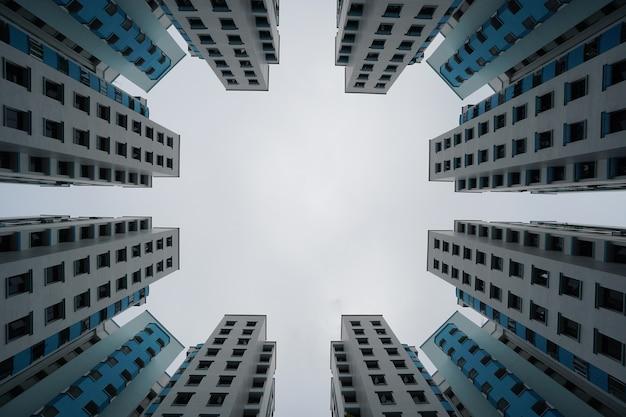 Vista de baixo ângulo de edifícios modernos em azul e branco sob um céu nublado