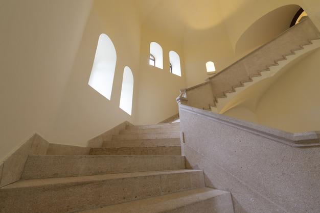 Vista de baixo ângulo de escadas brancas como leite ao lado das janelas durante o dia