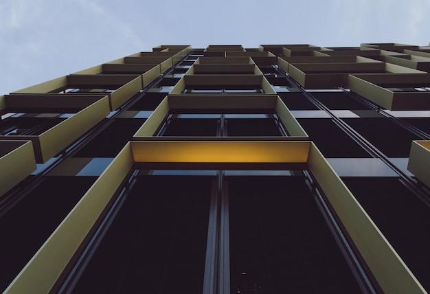 Vista de baixo ângulo de um edifício moderno com janelas de vidro sob a luz do sol