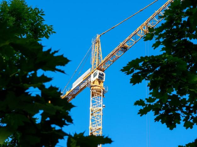Vista de baixo ângulo de um guindaste de torre de construção através da folhagem verde. fundos para construção civil