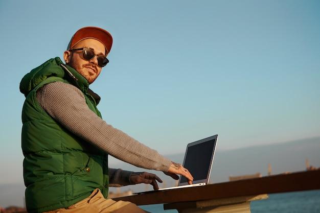 Vista de baixo ângulo de um jovem elegante e moderno, com barba por fazer, usando um dispositivo eletrônico genérico