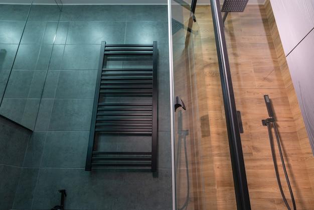 Vista de baixo ângulo de um toalheiro aquecido na parede de um banheiro com azulejos cinza ao lado de um box com decoração em padrão de madeira e porta de vidro aberta