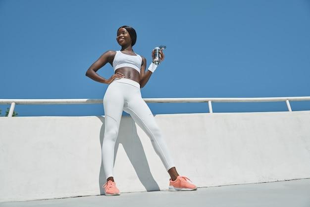 Vista de baixo ângulo de uma bela jovem africana em roupas esportivas, segurando uma garrafa com água
