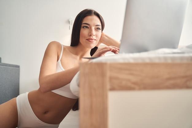 Vista de baixo ângulo de uma jovem sorridente em roupas íntimas da moda, sentada no chão e usando o laptop no quarto