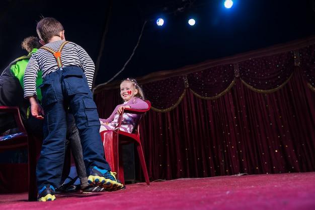 Vista de baixo ângulo de uma menina sorridente usando palhaço maquiagem sentada na cadeira vermelha no palco com um menino e um homem olhando, espaço de cópia à direita da imagem