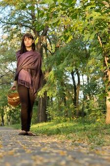 Vista de baixo ângulo de uma mulher morena atraente com uma cesta de maçãs em uma passarela na floresta