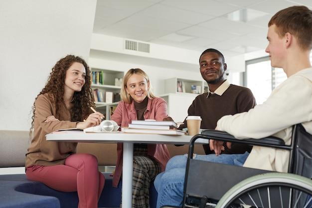 Vista de baixo ângulo em um grupo multiétnico de alunos estudando na biblioteca da faculdade, apresentando um jovem usando uma cadeira de rodas em primeiro plano