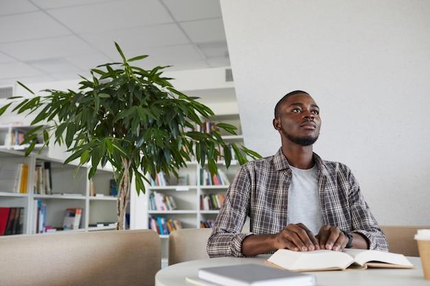 Vista de baixo ângulo para um homem afro-americano cego lendo livro em braille na biblioteca da escola,