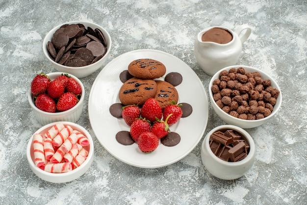 Vista de baixo, biscoitos de chocolate, morangos e chocolates redondos no prato oval branco e tigelas com doces, morangos, chocolates, cereais e cacau no fundo branco-acinzentado