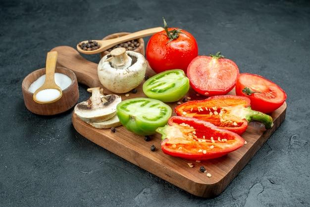 Vista de baixo, cogumelos de legumes frescos cortam tomates vermelhos e verdes pimentões em tigelas de tábua de cortar com pimenta preta e colheres de pau de sal na mesa escura