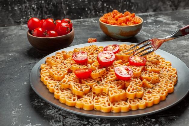 Vista de baixo corações de massa italiana cortam tomate cereja em prato oval garfo tomate cereja e macarrão coração vermelho em tigelas na mesa cinza