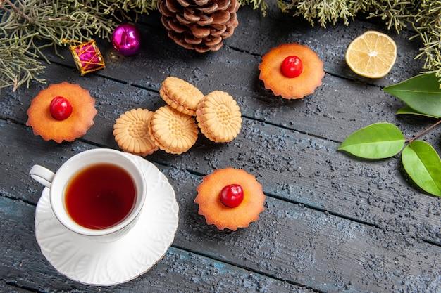 Vista de baixo cupcakes de cereja ramos de árvore de abeto fatia de limão uma xícara de biscoitos de chá na mesa de madeira escura