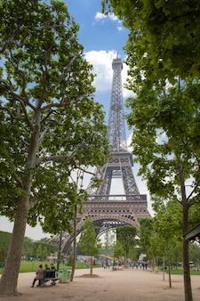 Vista de baixo da torre eiffel e de um belo parque verde