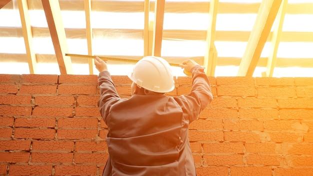 Vista de baixo das costas do homem usando capacete de segurança medindo a largura do teto com vigas de madeira