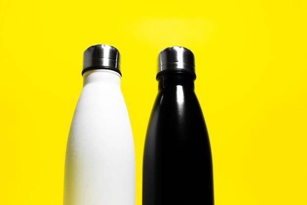 Vista de baixo de duas garrafas meio reutilizáveis de eco, aço inoxidável, garrafa térmica