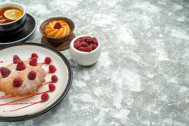 Vista de baixo de uma xícara de chá com rodelas de limão e bolo de baga de canela em uma placa oval branca em um local de cópia de superfície cinza