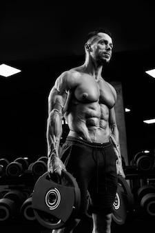 Vista de baixo do fisiculturista masculino sem camisa carregando pesos nos braços.