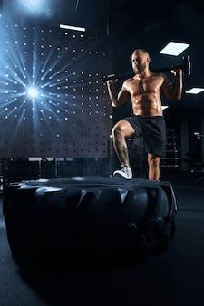 Vista de baixo do homem forte musculoso bonito segurando uma grande marreta atrás do pescoço.