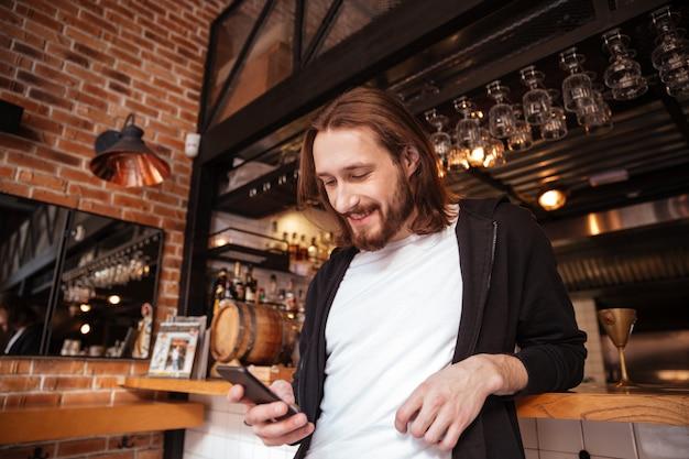 Vista de baixo do homem na barra com telefone
