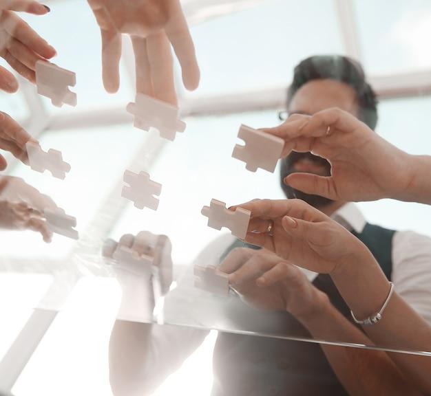 Vista de baixo. equipe de negócios dobrando peças do quebra-cabeça. conceito de uma startup