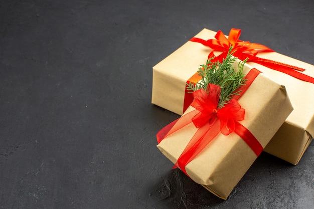 Vista de baixo, grandes e pequenos presentes de natal em papel pardo amarrado com fita vermelha no espaço livre escuro