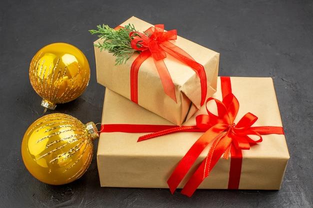 Vista de baixo, grandes e pequenos presentes de natal em papel pardo, amarrados com bolas de fita vermelha de ano novo no escuro