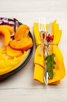 Vista de baixo, legumes e frutas picados, abóbora, pimentão, caqui na placa preta, garfo e faca no guardanapo amarelo na superfície branca