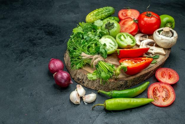 Vista de baixo legumes frescos cogumelos tomates vermelhos e verdes pimentões vermelhos verdes pepinos no tabuleiro rústico pimentas cebolas alho na mesa preta com espaço livre