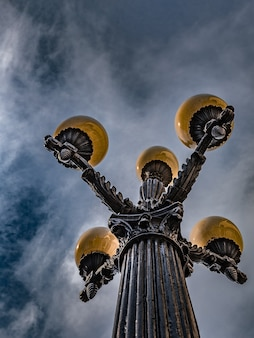 Vista de baixo para cima de um poste de rua vintage de ferro fundido contra um céu azul rico com nuvens cirros claras