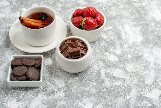 Vista de baixo para tigelas com morangos e chocolates e chá de sementes de anis de canela no canto superior esquerdo do fundo branco-acinzentado