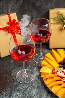 Vista de baixo, pedaços de queijo, carne, uvas e romã, em um tabuleiro oval, uma taça de vinho apresenta-se em um fundo escuro