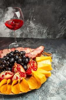 Vista de baixo, pedaços de queijo, carne, uvas e romã em uma taça oval de vinho em fundo escuro.