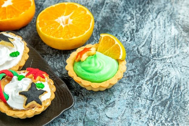Vista de baixo, pequenas tortas de natal em uma placa preta cortam laranjas na mesa cinza