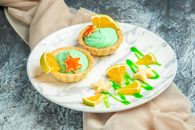 Vista de baixo tortinhas com creme verde e rodela de limão em um prato de xale bege na superfície escura