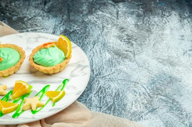 Vista de baixo tortinhas com creme verde e rodela de limão no prato, corte laranjas em superfície escura e coloque