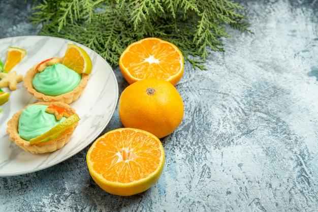 Vista de baixo tortinhas com creme verde e rodela de limão no prato, corte laranjas em superfície escura, espaço livre