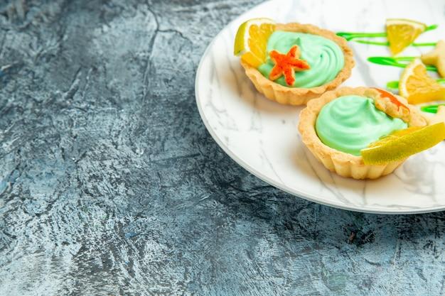 Vista de baixo tortinhas com creme verde e rodela de limão no prato em superfície escura e local livre