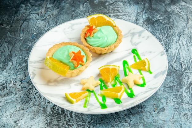 Vista de baixo tortinhas com creme verde e rodela de limão no prato em superfície escura