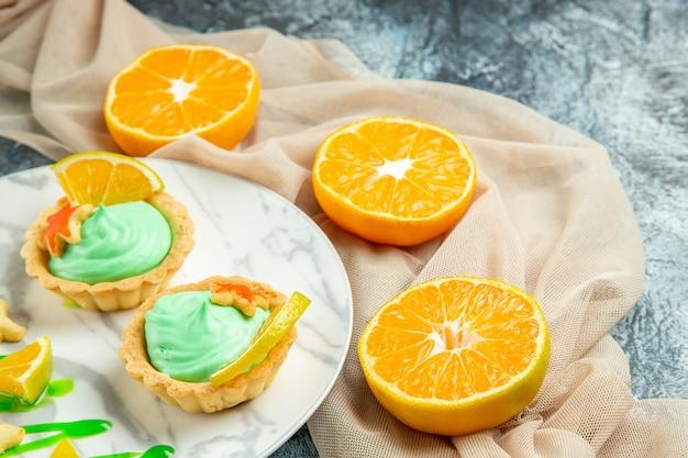 Vista de baixo tortinhas com creme verde e rodela de limão no prato sobre xale bege e laranjas cortadas na superfície escura