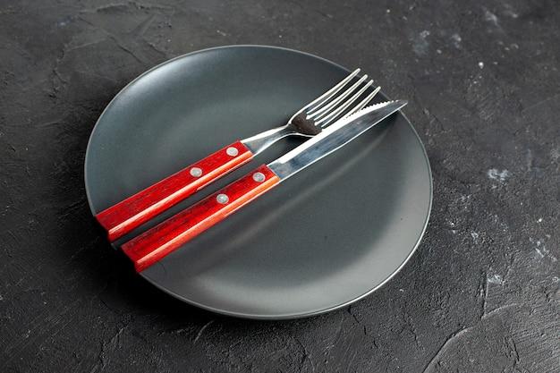 Vista de baixo, um garfo e uma faca em uma travessa redonda preta em uma superfície escura