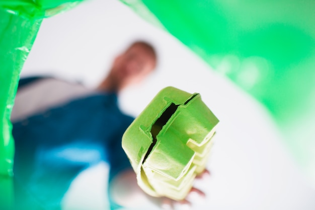 Vista de baixo. um homem joga lixo de papelão em uma cesta especialmente projetada para lixo de papelão