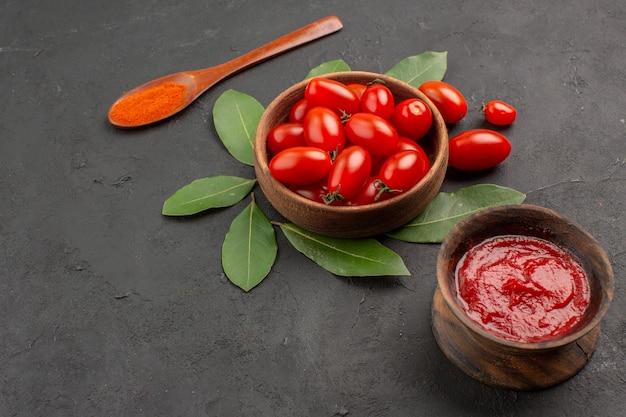 Vista de baixo, uma tigela de louro de tomate cereja deixa uma colher de pau e uma tigela de ketchup na mesa preta