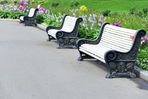 Vista de bancos no parque, gramado e flores