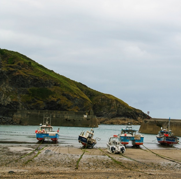 Vista de barcos em uma praia arenosa com uma montanha e um céu nublado
