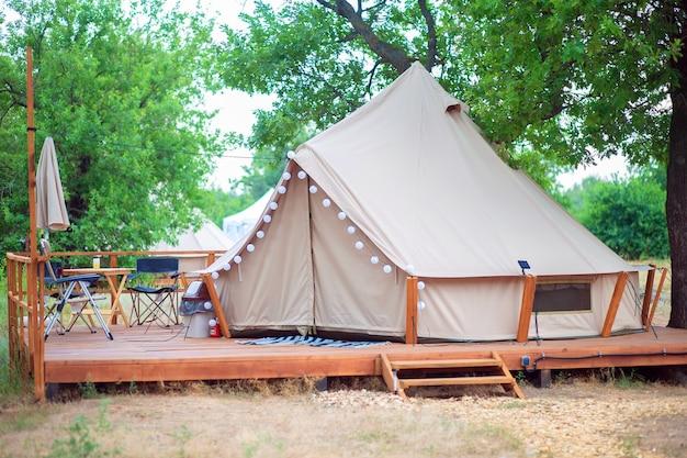 Vista de barracas de camping modernas na área glamping. tenda de acampamento com todas as comodidades. civilização na floresta. tenda com luz e móveis
