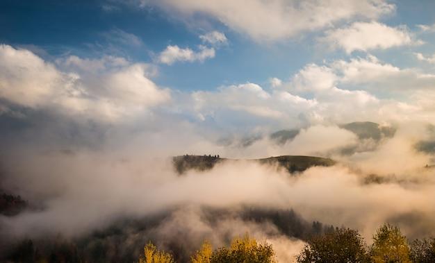 Vista de belas colinas rodeadas por densa névoa.