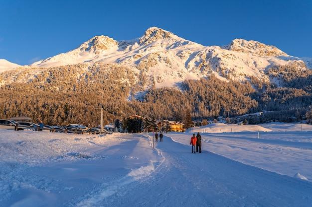 Vista de belas montanhas de neve perto do lago silvaplana, na suíça, durante uma noite fria de inverno ao pôr do sol