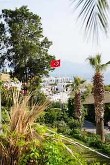 Vista de bodrum sity, palmeiras, mar e a bandeira da turquia
