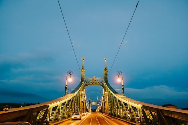 Vista de carros passando à noite na ponte da liberdade em budapeste
