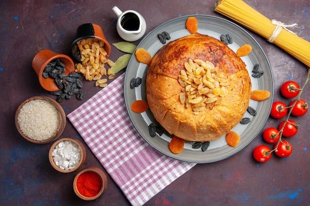 Vista de cima, a deliciosa refeição oriental do shakh plov consiste em arroz cozido dentro de uma massa redonda em um piso escuro.